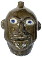 "B384  Face Jug, stoneware North Carolina  Ceramic Teeth, Alkaline Glaze, Applied Handles, 12"" tall,  runny alkaline glaze, clay eyes with cobalt pupils"