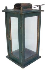 "X119 Mid-19th century, pinned construction. Four windows are contained within a wooden box frame that is  pine; uprights having beaded edges. One side with a hing  door providing access to candle. Interior is fitted with a tin candle tray; top having a wrought loop handle with tin ventilator; all glass appears to be of the period. In an old dark green paint  measurements are 71/4"" x 7 1/4"" x 15 1/4"" tall"