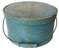 "RM748 19th century New England Bail Handle Pantry Box with the original dry blue paint ,with over lapping bentwood sides, secured with small metal tacks. The sides of the Box are fitted with a pair of oval stamped tin  handle mounts. Fitted with an arched wire swing handle with wooden hand grips.  11 1/2"" diameter x 6 1/2"" tall"