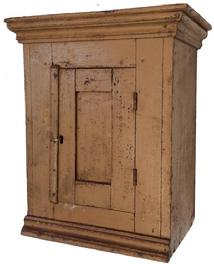 A400  19th century Pennslyvania Hanging wall cabinet, with old mustard paint, single door  with in set panel, applied molding  to top and below door, it is pit sawed  one board construction ,