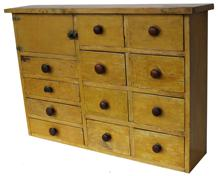 SOLD B220 Late 19th century twelve drawer Apothecary Chest, unusual form having a single door on one side, square head nail construction, in the original mustard paint.