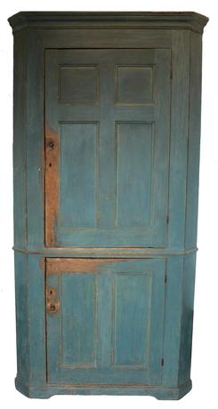 C194 19th century Pennsylvania small Corner Cupboard, with the original blue paint, with the bible and  cross door at the top, with a double panel door at bottom, outstand two step cove molding at the top also with a small waist molding . Applied bracket base, it retains it�s original small wooden knobs. the shelves are beaded front. the wood is pine, circa 1820 ,Lancaster or  Berks County Pa  . Measurements are 76� tall x takes a 26� corner