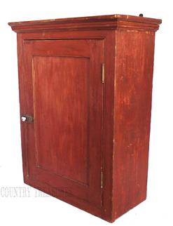 C214Mid 19th century New England original red painted Hanging Cupboard, single panel door full mortised with a beaded edge around door, square head nail construction, small applied molding