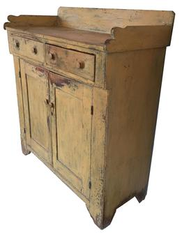 (L276) Found in Lancaster Pennsylvania still retains it old mustard paint showing great wear to the paint on the drawers and door. It has two drawers  which are dovetailed, and two doors with inset panels, and a nice high foot, with a cut  out design. Circa 1830's
